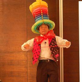 カラフルなバルーンで作った帽子を被ってバルーンショーをする風船太郎