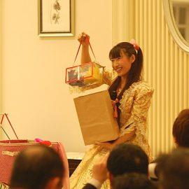 企業パーティーで笑顔でマジックを披露する女性マジシャン・荒木巴