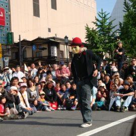 大勢の観客の前でパフォーマンスをする大道芸人「ミスターバード」