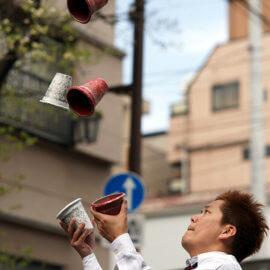 シェーカーカップでジャグリングをする大道芸人