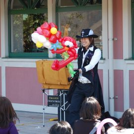 大きなバルーンの作品を笑顔で観客に見せるパフォーマー