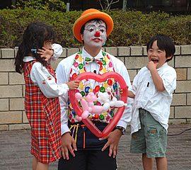 クラウン(ピエロ)姿でバルーンを作って子供を笑顔にする大道芸人