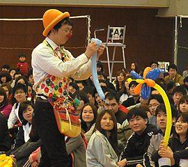 体育館でのイベントで次々にバルーンを作って観客を楽しませる大道芸人