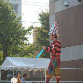 ステージで軽快なトークを織り交ぜたバルーンショーをする男性パフォーマー