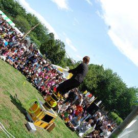 ローラーを積み重ねた上に乗るバランス芸を披露する大道芸人