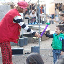 小さな男の子にバルーンを作って渡すクラウン(ピエロ)