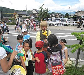 バルーングリーティングをして子ども達に囲まれるクラウン(ピエロ)