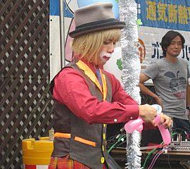 クラウン(ピエロ)の衣装でバルーンショーをする大道芸人