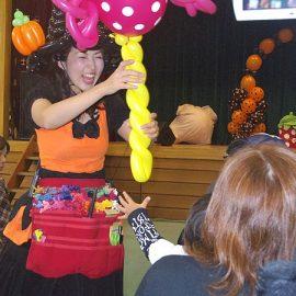 ハロウィンイベントで大きな飴玉のバルーンを女の子にプレゼントする女性パフォーマー