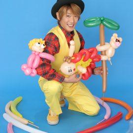 可愛らしいキャラクターのバルーンを持つ大道芸人