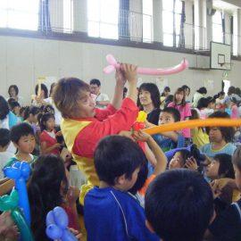 お子様に囲まれてバルーンアート教室をする大道芸人