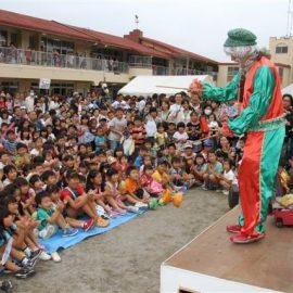 たくさんの観客に囲まれてパフォーマンスをするクラウン(ピエロ)