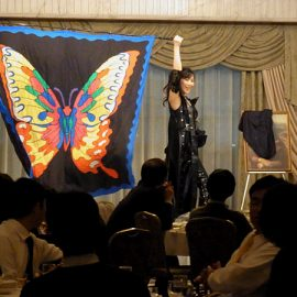 企業の忘年会パーティーでショーをする女性マジシャン