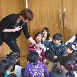 子ども達の前でマジックショーをするマジシャン