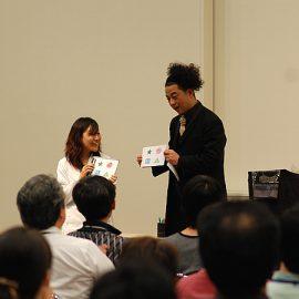 観客の女性と共にマジックを披露するマジシャン