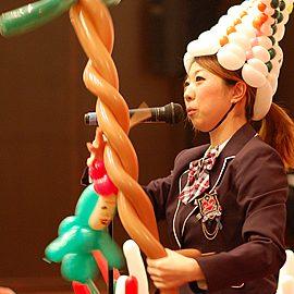 バルーンアートとマジックを構成に入れたショーをする女性パフォーマー