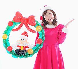 クリスマス衣装でツリーとサンタのバルーンを作るバルーンパフォーマー