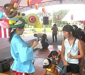 お祭りで子ども達の要望に応じてバルーンアートを作るパフォーマー