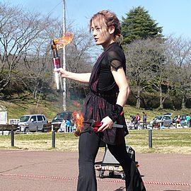 火の付いた棒でジャグリングをする世界レベルのジャグリングパフォーマー
