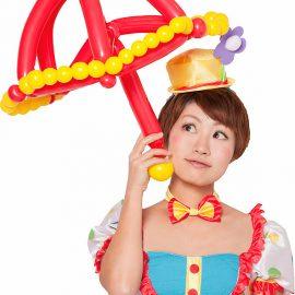 バルーンでできた傘を持ってポップな衣装で写る女性パフォーマー