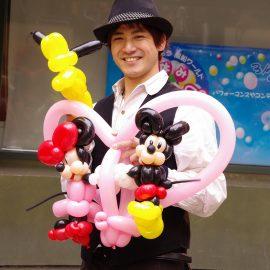 有名キャラクターのバルーンアートを持つ男性パフォーマー