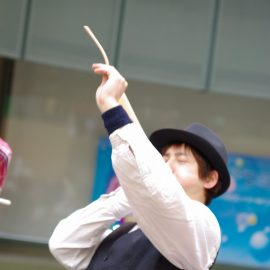 バルーンアート用の長い風船を膨らませる男性パフォーマー