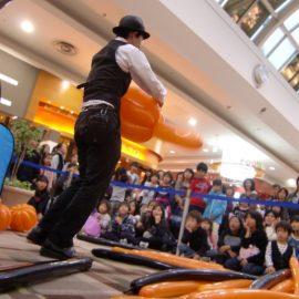ハロウィンイベントでかぼちゃのバルーンアートを作る男性パフォーマー