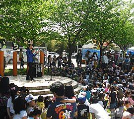 広場のステージ上で観客に取り囲まれながらジャグリングショーをする男性パフォーマー