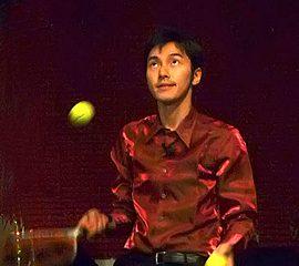 テニスラケットとボールを使ったオリジナルの技を披露する男性ジャグラー