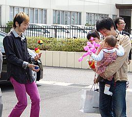 小さいお子様を連れたご家族の前でボールジャグリングをするジャグリングパフォーマー