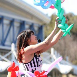 色とりどりの風船で可愛いバルーンアートを作る女性パフォーマー