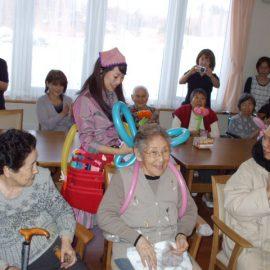 高齢者施設でバルーンアートショーをする女性バルーンパフォーマー