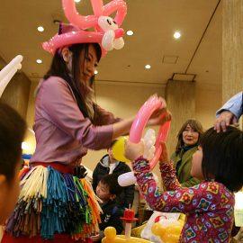 女の子にピンクの可愛いバルーンアートを作ってプレゼントする女性パフォーマー