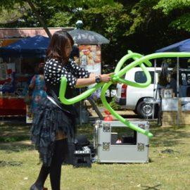 芝生広場でのイベントでお客様の目の前でバルーンを作る女性パフォーマー