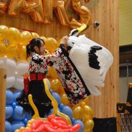 和風の衣装で出演して鶴のバルーンを作る女性パフォーマー