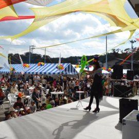 祭りのステージでバルーンアートショーをする女性パフォーマー
