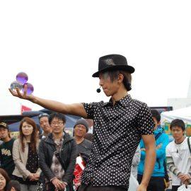 たくさんの観客の前で3つの水晶玉を使ったコンタクトジャグリングをする大道芸人