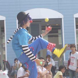 コミカルな衣装でボールジャグリングをするクラウン(ピエロ)
