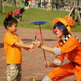 ハロウィン衣装で男の子に皿回しを教えるクラウン(ピエロ)
