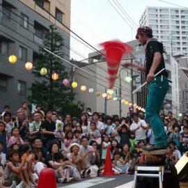 多くの観客の前でバランスを取りながらカラーコーンでジャグリングをする大道芸人