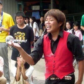 水晶玉でコンタクトジャグリングをする大道芸人