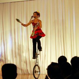 高い一輪車に乗ってジャグリングをするという難しい技を披露する女性ジャグラー