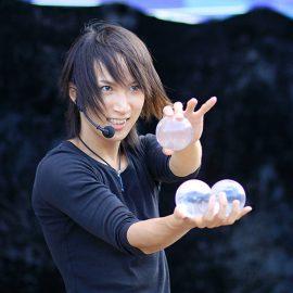 水晶玉のコンタクトジャグリングをする男性ジャグラー