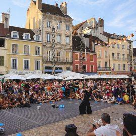 海外で多くの観客に囲まれてショーをする男性ジャグラー
