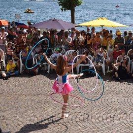 外国の路上でお客様に囲まれる中フラフープを使ったショーを披露する女性ジャグリングパフォーマー