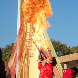 口から火を噴くパフォーマンスをする大道芸人