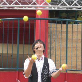 ポップな曲に乗せてボールジャグリングをする大道芸人