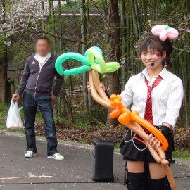 屋外会場でバルーンアートショーをする女性パフォーマー