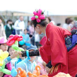 観客のお子様に花のバルーンをプレゼントするバルーンパフォーマー