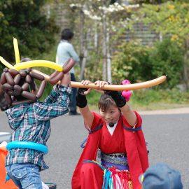ショー中にバルーンで作った剣で男の子と戦う仕草をするバルーンパフォーマー
